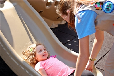 Laughing child on slide with young woman assisting her