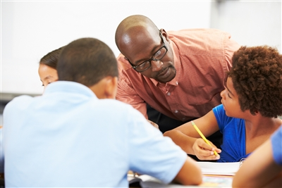 Adult tutoring three children of different races