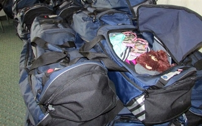 A pile of duffle bags full of clothes and comfort toys for human trafficking victims