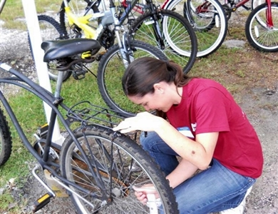 Sarah Scharf of East Lake ToyMakers works one in a row of bikes