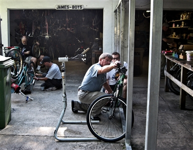 "Volunteers working on bikes in a shop under the name ""James Boys"""