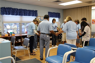 Prayer circle of volunteers in waiting room as people wait outside the window