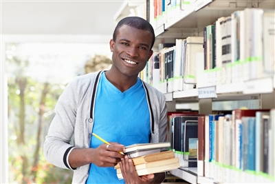 Stock photo of smiling male African American college student in library