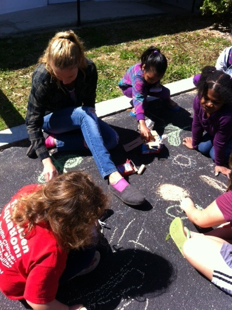 Children make chalk drawings on the pavement outside Derbyshire Place