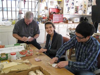 Three volunteers hand-sand wood pieces to make toys