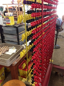 Hundreds of tiny painted red and yellow wheels dry on racks