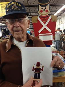 Volunteer Bob Pollard shows the tiny version of a toy soldier