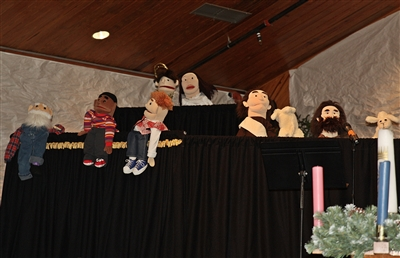 A variety of puppets on black-shrouded stage