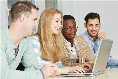 Ethnically mixed group of students looking at laptop computer